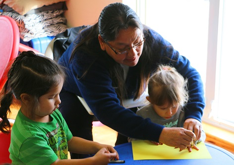 An instructor leads children through a drawing exercise at Lakota Immersion Childcare