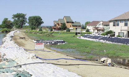 Multiple pump hoses carry groundwater over a dike in rural Union County, S.D.