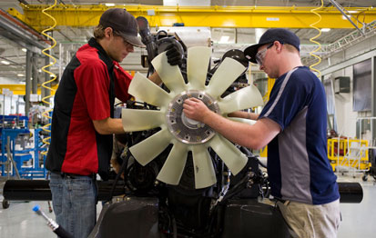 Workers readying an engine at the AGCO plant in Jackson, Minn.