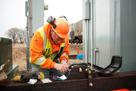 Canadian Pacific assistant signalman Mark Hasen wires a switch circuit controller as part of the installation of centralized traffic control near Hankinson, N.D.